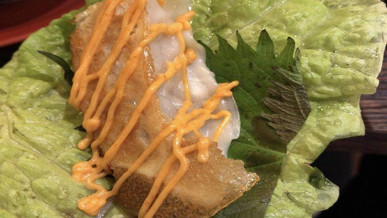 サンチュと大葉、コチュジャンとマヨネーズを混ぜた特製ソースをかけて食べる焼き餃子