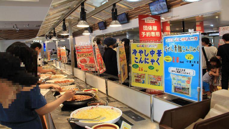 たくさんの人が色んなこんにゃく料理を並びながら選んでいる